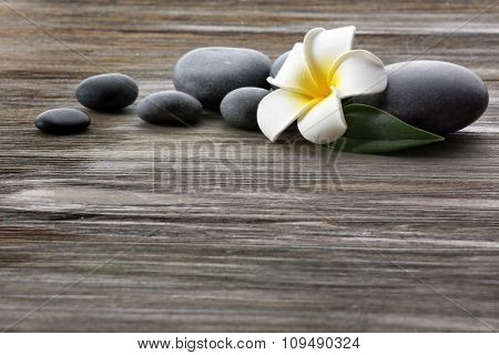 Spa stones with flower on wooden background