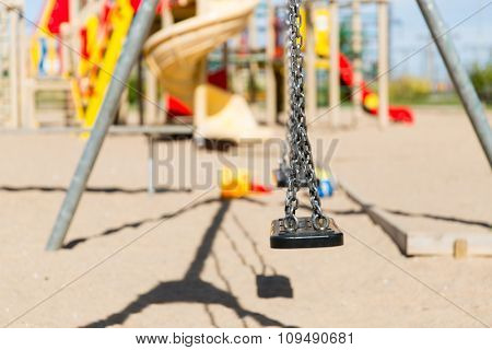 childhood, equipment and object concept - close up of swing on playground outdoors at summer