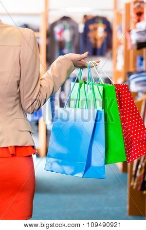 Woman with shopping bags in shop