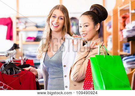 Asian and Caucasian Women friends shopping in boutique or fashion store
