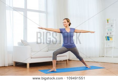 fitness, sport, people and healthy lifestyle concept - woman making yoga warrior pose on mat