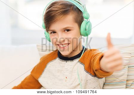 leisure, children, technology, gesture and people concept - smiling boy with headphones listening to music and showing thumbs up at home