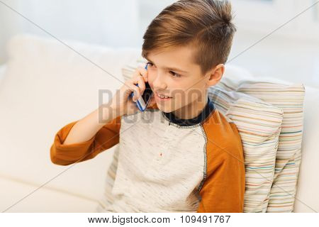 leisure, children, technology, communication and people concept - smiling boy calling on smartphone at home