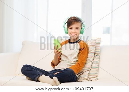 leisure, children, technology and people concept - smiling boy with smartphone and headphones listening to music at home