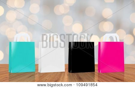 sale, consumerism and advertisement concept - many blank shopping bags blue, white, black and pink color over holidays lights background