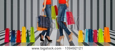 people, sale and consumerism concept - close up of women with shopping bags over gray striped 3d background