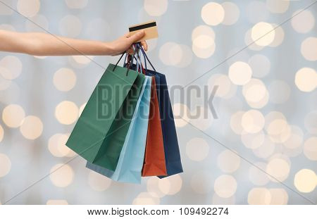 people, sale and consumerism concept - close up of woman with shopping bags and bank or credit card over holidays lights background