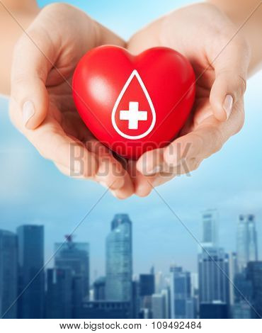 healthcare, medicine and blood donation concept - female hands holding red heart with donor sign over city buildings background