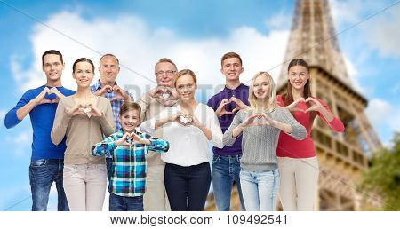 gesture, family, travel and tourism concept - group of smiling people  showing heart shape hand sign over eiffel tower background