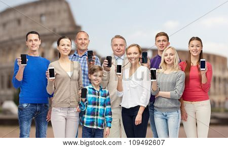 family, technology, travel and tourism concept - group of smiling people with smartphones over coliseum background