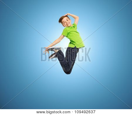 happiness, childhood, freedom, movement and people concept - smiling boy jumping in air over blue background