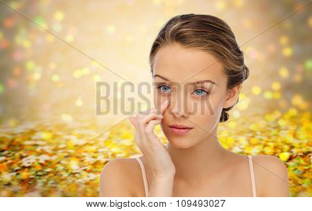 beauty, people, cosmetics, skincare and health concept - young woman applying cream to her face over golden holidays lights or yellow glitter background