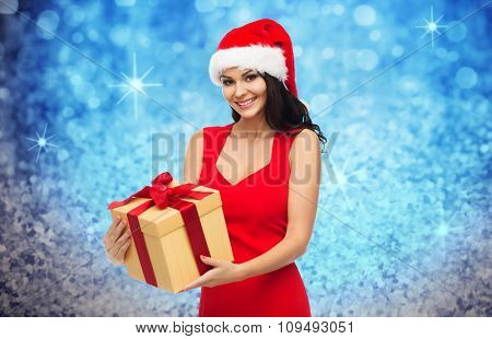 people, holidays, christmas and celebration concept - beautiful sexy woman in red dress and santa hat with gift box over blue glitter and lights background