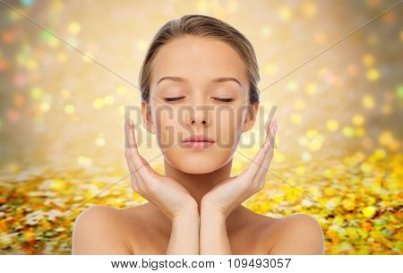 beauty, people, skincare and health concept - young woman face and hands over golden holidays lights or yellow glitter background