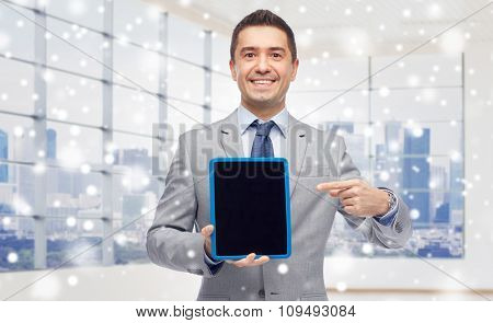 business, people and technology concept - happy smiling businessman in suit showing tablet pc computer black blank screen over city office window background and snow effect