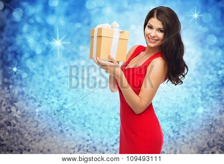 people, holidays, christmas, birthday and celebration concept - beautiful sexy woman in red dress with gift box over blue glitter and lights background