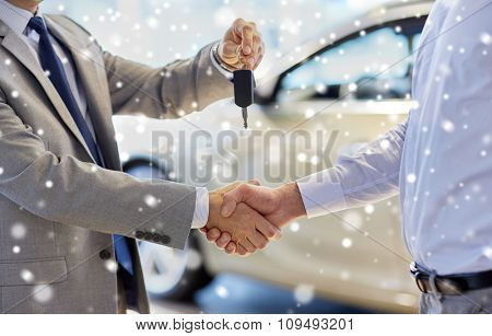 auto business, car sale, deal, gesture and people concept - close up of dealer giving key to new owner and shaking hands in auto show or salon over snow effect