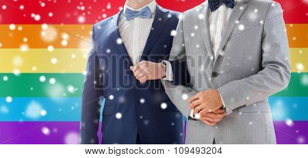 people, homosexuality, same-sex marriage and love concept - close up of happy male gay couple holding hands on wedding over rainbow flag background and snow effect