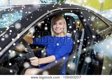 auto business, car sale, consumerism , transportation and people concept - happy woman sitting in or driving car over snow effect