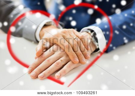 people, homosexuality, same-sex marriage and love concept - close up of happy male gay couple hands with wedding rings on and red heart shape over snow effect
