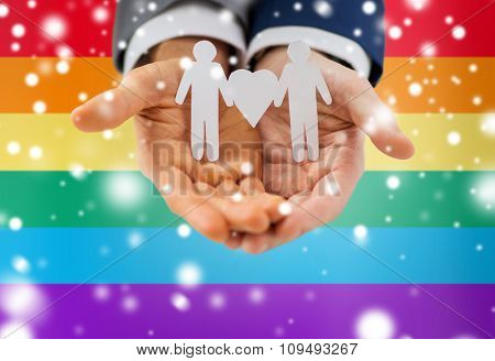 people, homosexuality, same-sex marriage and love concept - close up of happy male gay couple holding paper cutout love symbol over rainbow flag background and snow effect