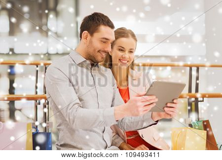 sale, consumerism, technology and people concept - happy young couple with shopping bags and tablet pc computer in mall with snow effect