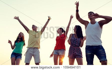 friendship, summer vacation, holidays, party and people concept - group of smiling friends dancing on beach