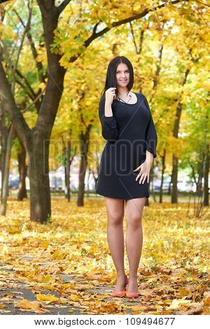 beautiful girl in black dress and red shoes in yellow city park, fall season
