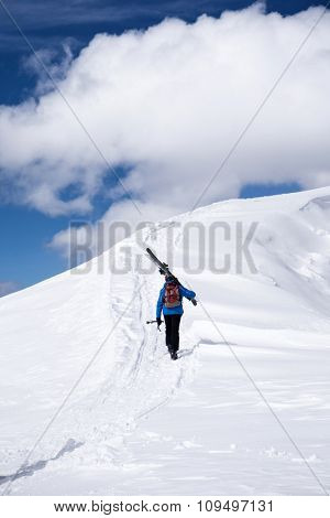 Skier climbing a snowy mountain, extreme winter sport