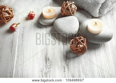 Composition of flowers, candles and stones on white wooden background, in spa salon