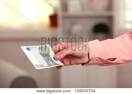 Woman holding Euro banknote in the room