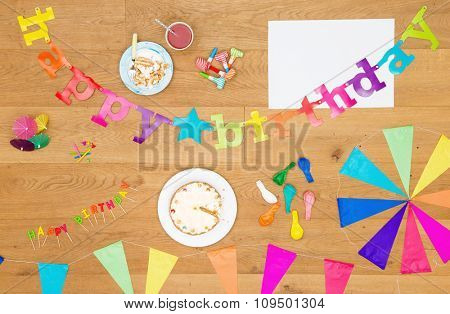 Assorted array of birthday party items and objects, such as cake, candles, garlands, whistles, balloons and such on a wooden surface, including a white sheet for copy space, seen from above.