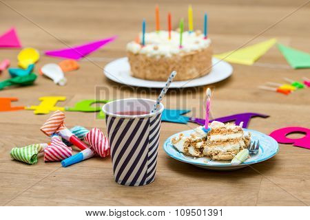 Happy birthday party still life with various garlands and objects, including a plate with cake and a candle and a paper cup with lemonade on a wooden surface