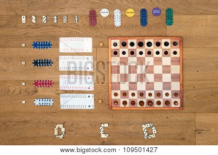 Top view of Board game items and gambling objects, such as a chess board and pieces, cards, chips, and dominoes neatly aligned on a wooden surface, seen from above