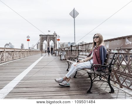 The Woman Is Sitting On A Bench On The Brooklyn Bridge And Looking At Skyscrapers Of New York.