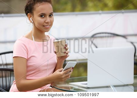 Young pretty woman in pink dress with laptop drinking coffee and listening music by headphones at summer terrace