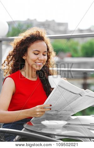Portrait of young pretty woman in red dress reading newspaper at summer terrace