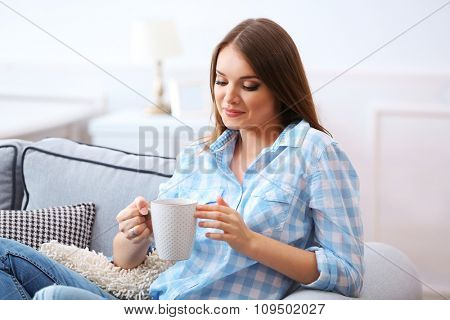Pretty young woman drinking tea at home