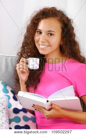 Young pretty girl in pink dress reading book and drinking coffee in the room