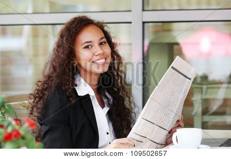 Young pretty business woman reads newspaper in the restaurant's terrace