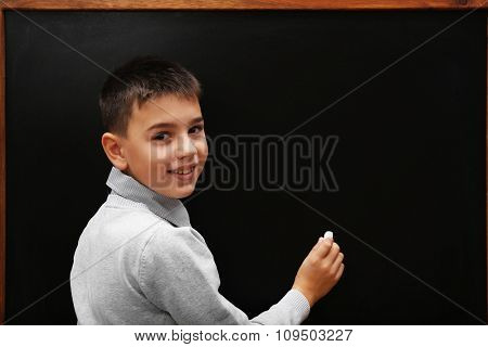 Young cute schoolboy writing at the blackboard