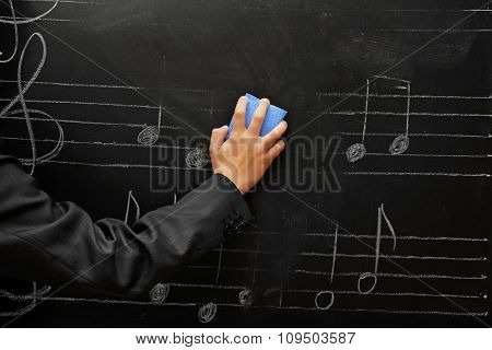 View on schoolboy's hand cleaning the blackboard with musical notes, close-up