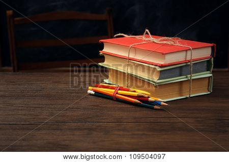 Colourful pile of books with pencils on wooden table
