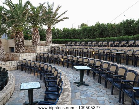Modern Amphitheater Plastic Chairs And Palm Trees In Greece