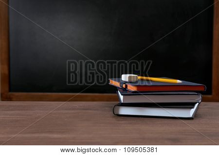 School equipment on desk on blackboard background
