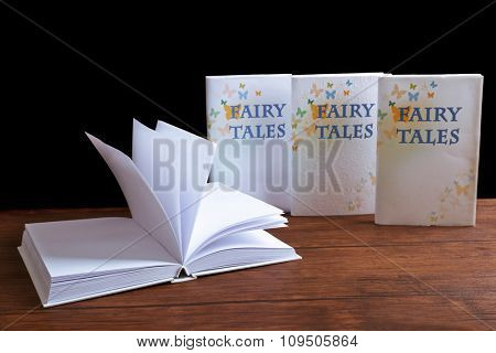 Books on the wooden table in front of black background