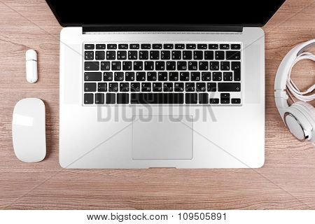 Close-up view of laptop and equipment at working place on brown wooden background