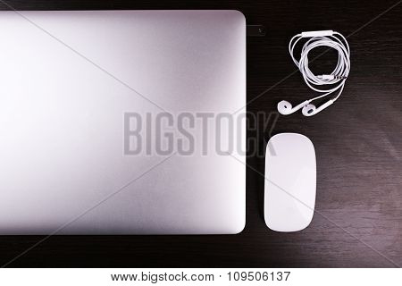 Close-up view of laptop and equipment at working place on black wooden background