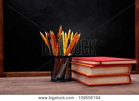 School equipment on desk on blackboard background