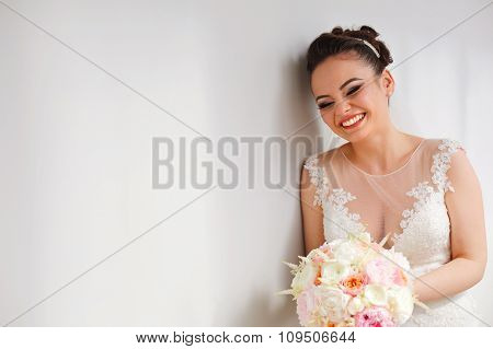 Joyfull Bride With Beautiful Bouquet Next To White Wall Isolated